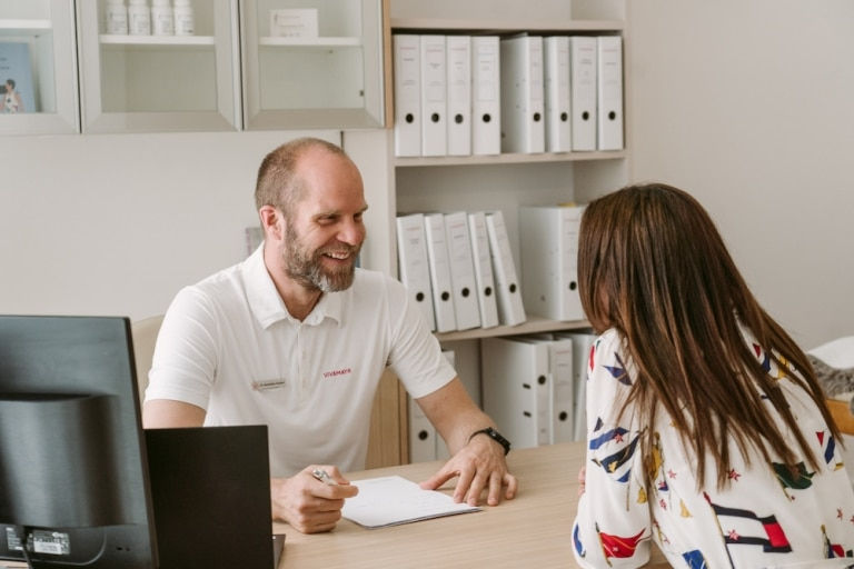 Dr. Schubert, head physician at VIVAMAYR Altaussee smiling at patient at VIVAMAYR Day Clinic in Vienna while giving her health advice