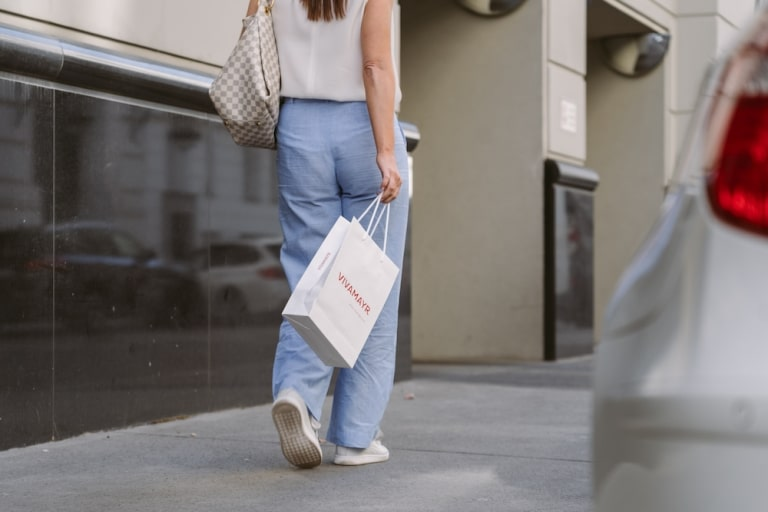 Woman leaving VIVAMAYR Day Clinic in Vienna, Austria with shopping bag