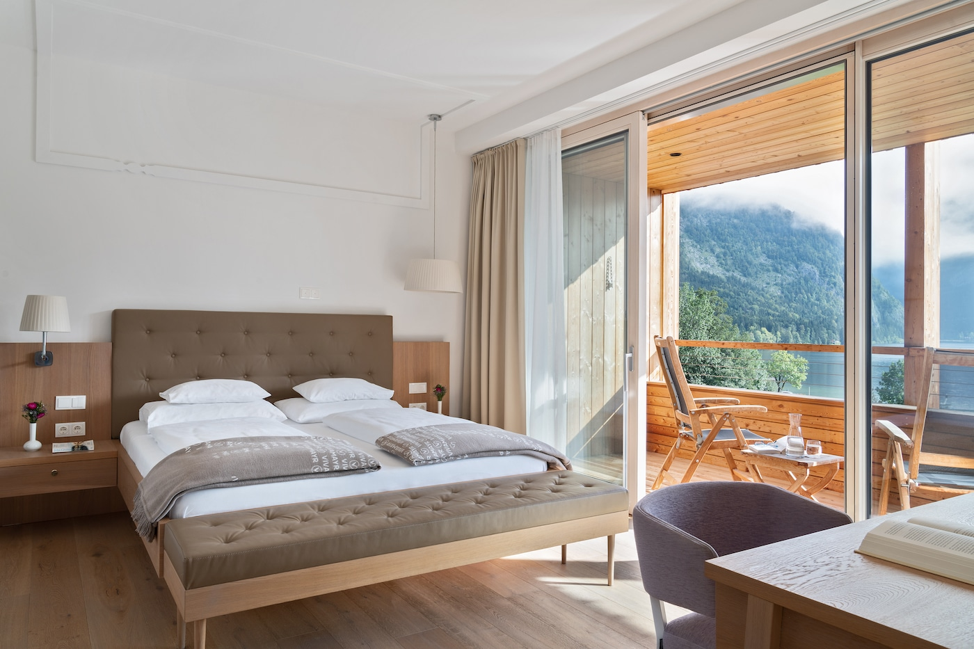 bright bedroom with wide windows in Junior Suite with lake view VIVAMAYR Altausee