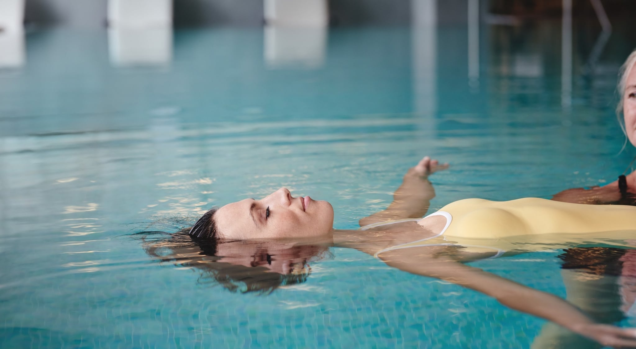 Female guest enjoying herself during WATSU (water shiatsu) session in pool at Medical Health Resort VIVAMAYR Altaussee