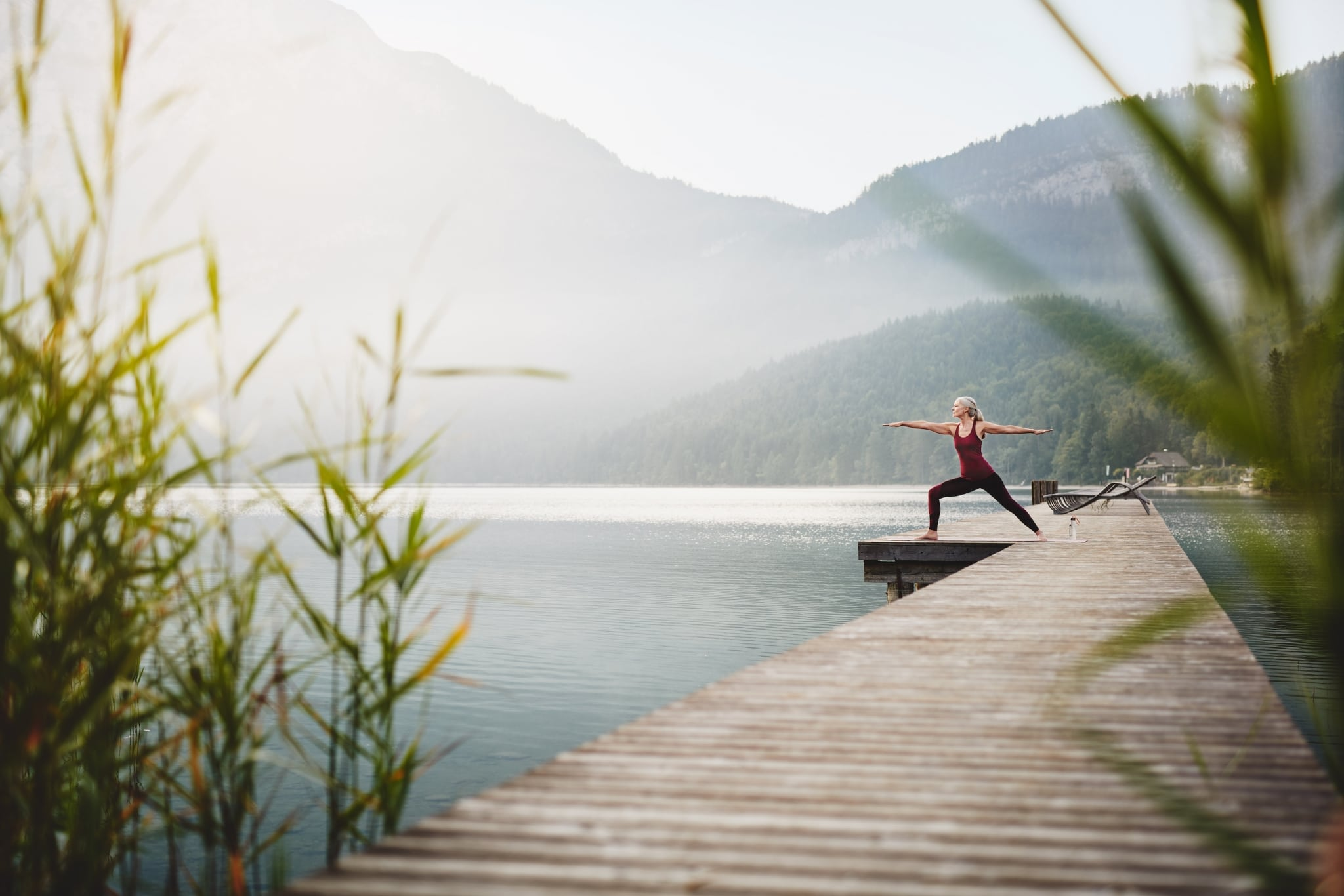 Woman doing yoga on a jetty with beautiful nature surrounding her