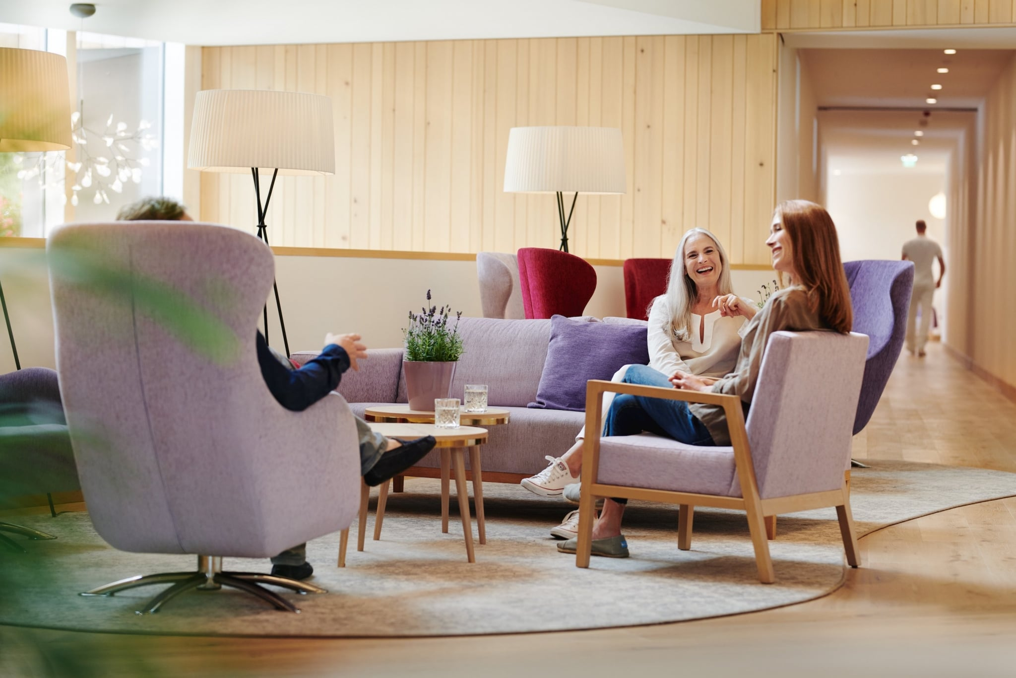 Two women sitting in modern purple armchairs at beautiful lobby at Medical Health Resort VIVAMAYR Altaussee smiling and having a chat