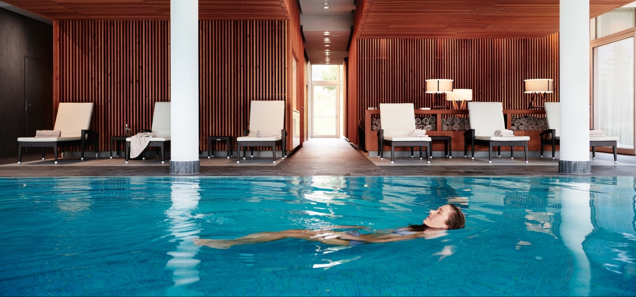 Young woman swimming on her back at exclusive pool and spa area of Medical Health Resort VIVAMAYR Altaussee