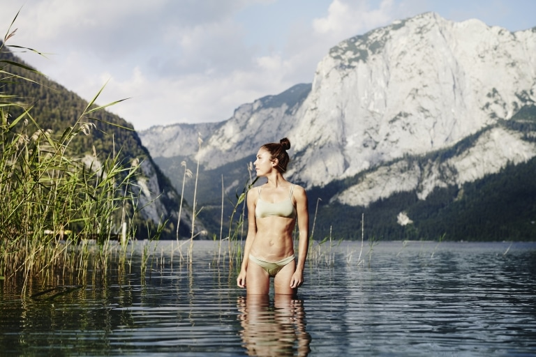 Woman standing up to knees in water of lake Altuassee with the Styrian mountains in the background