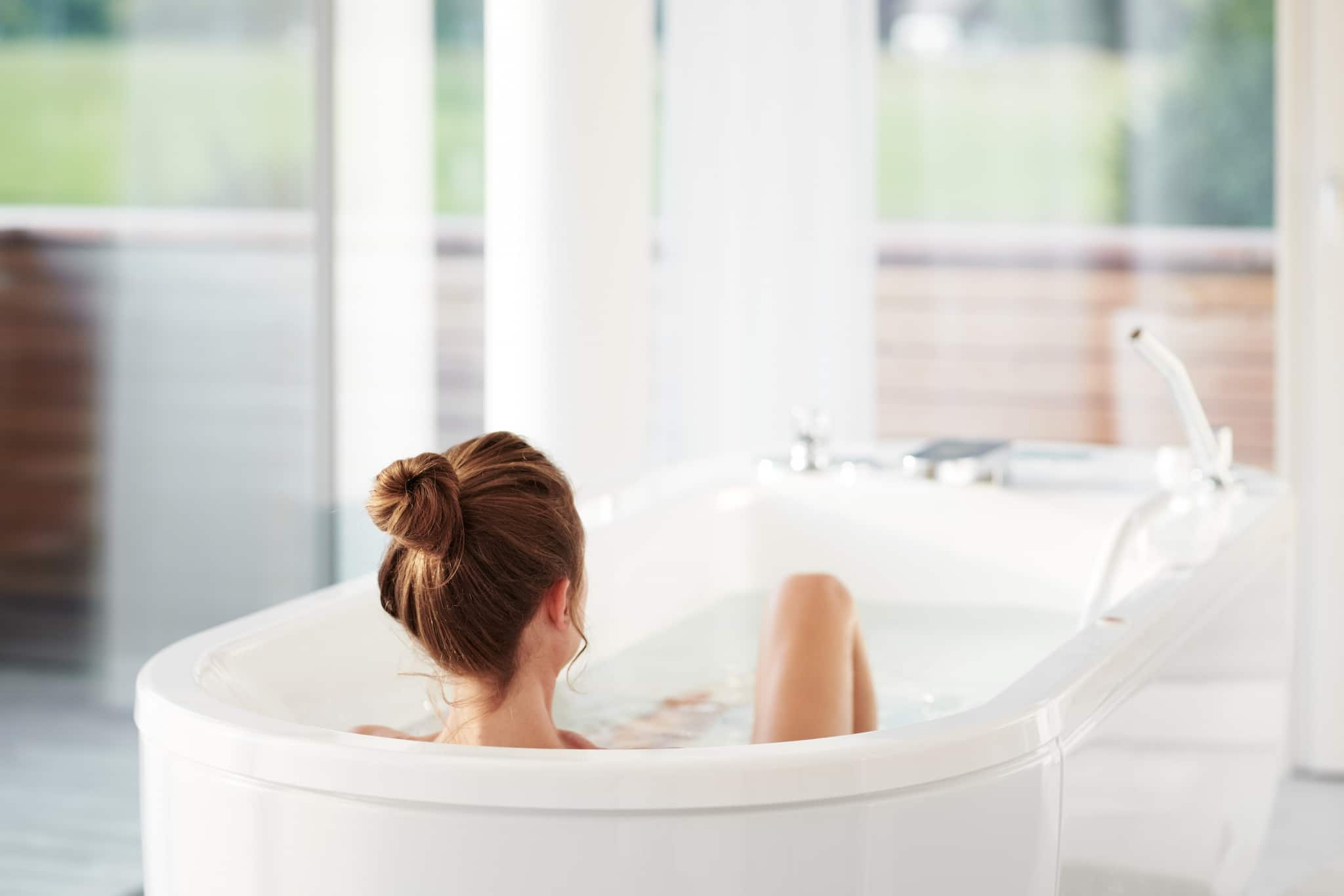 Young female with her hair in a bun relaxing in bathtub at Medical Health Resort VIVAMAYR Altaussee in Austria