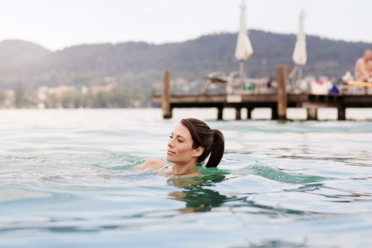 Woman swimming in the Lake Wörthersee with jetty in the background