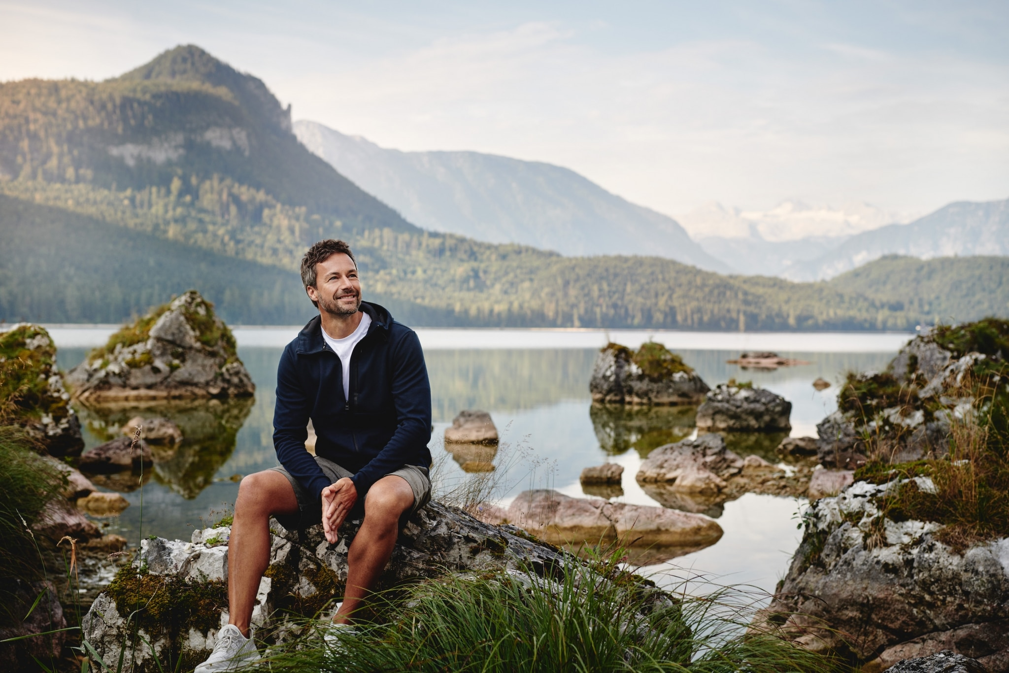 Man sitting on a rock in front of the lake Altaussee