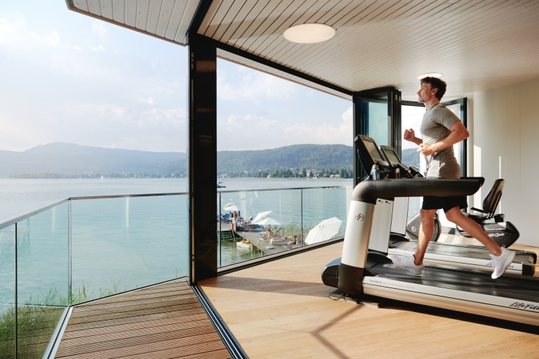 Male guest running on a treadmill while having a great view at the lake