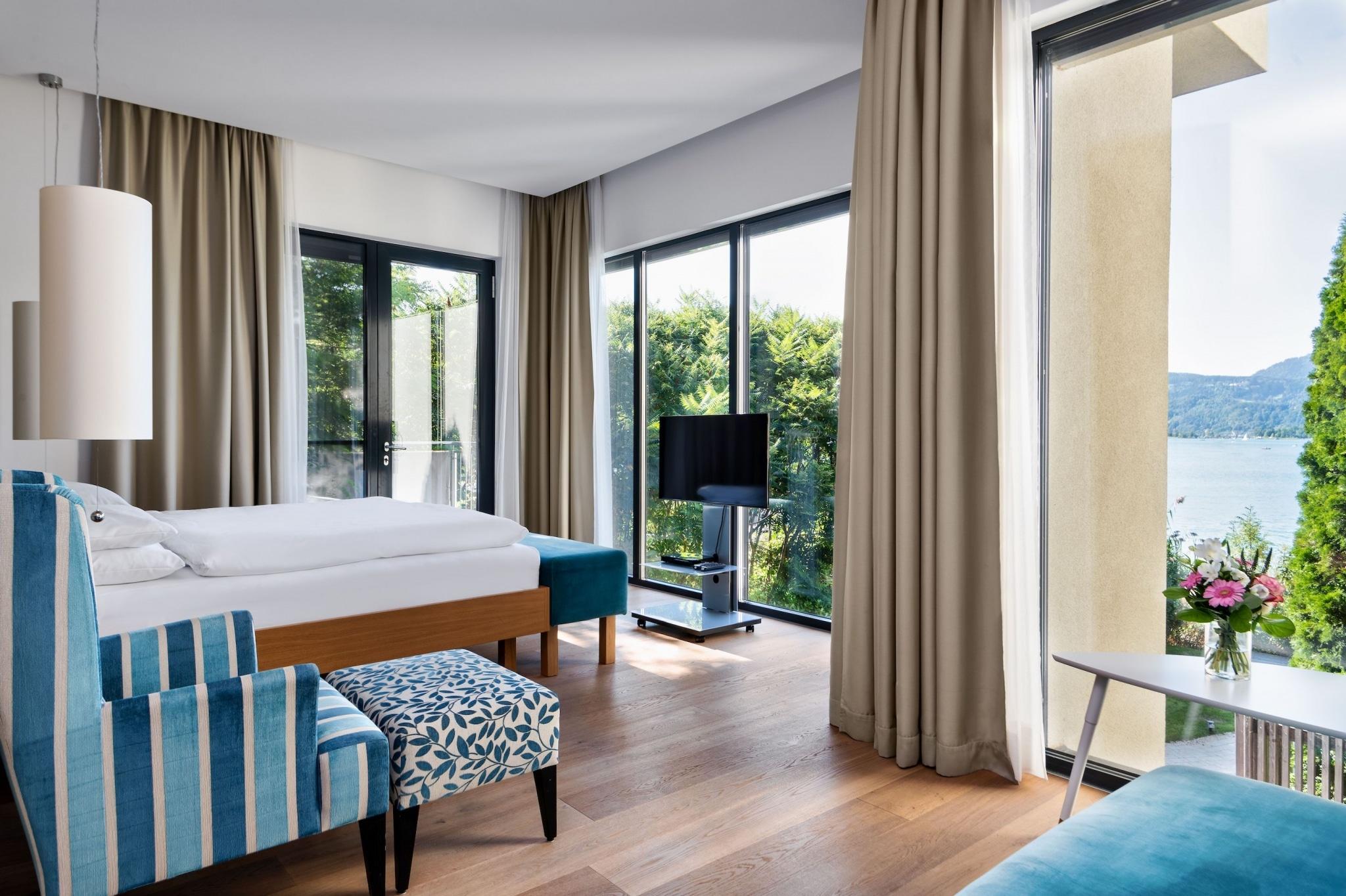 luxurious bedroom with many windows of a villa at VIVAMAYR Maria Wörth