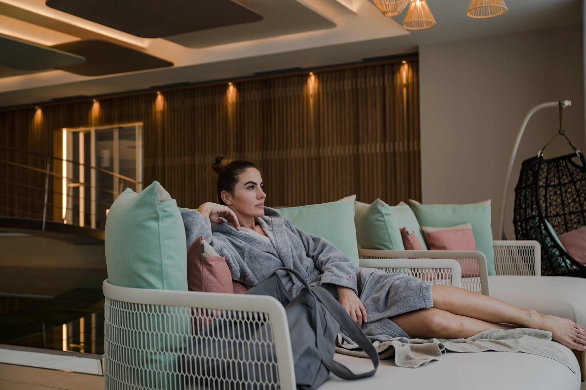 young female with a hair bun chills in a lounge furniture in the SPA