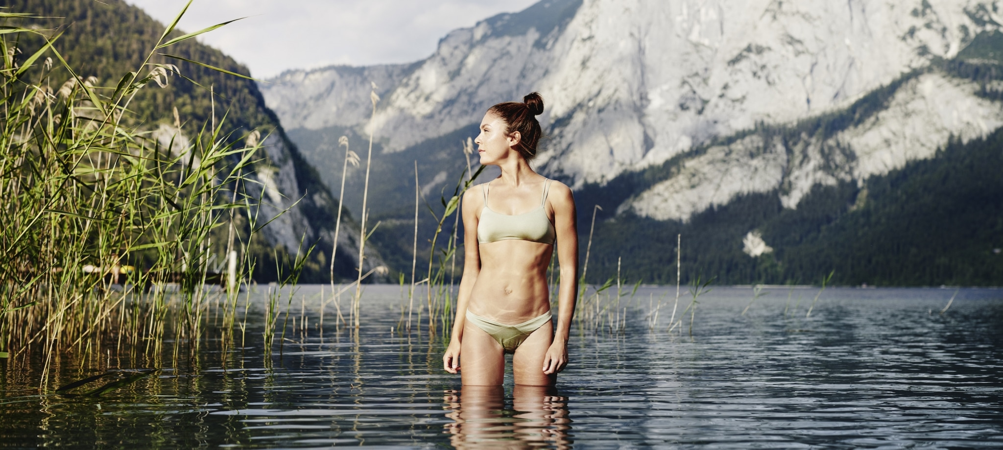 Young, fit woman wearing beige bikini going for a swim in lake Altaussee at Medical Health Resort VIVAMAYR Altaussee