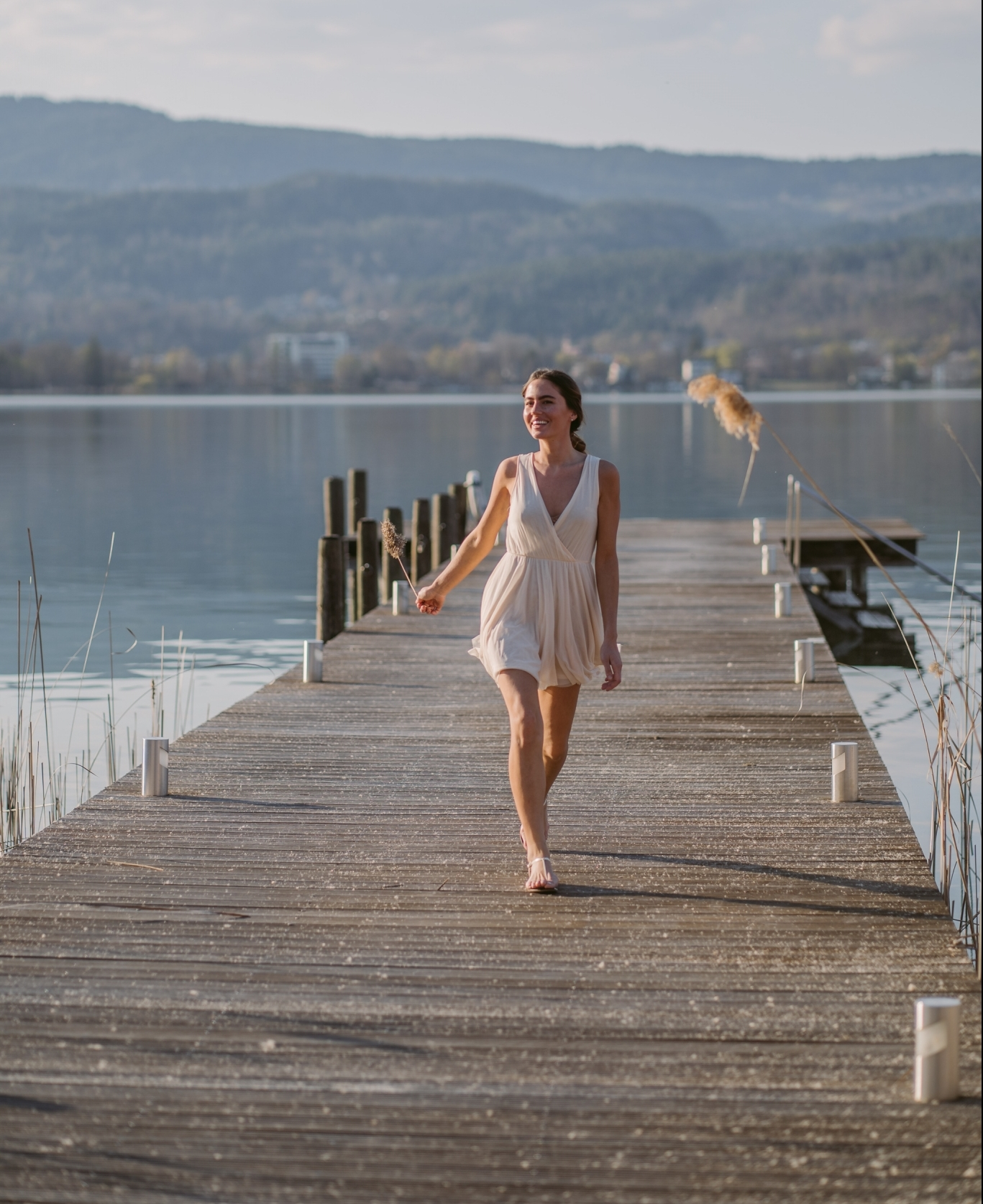 Woman in bright summer dress walking and smiling on private dock at VIVAMAYR Maria Wörth