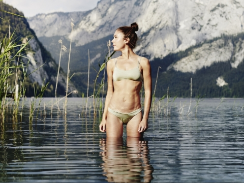 Woman standing up to knees in water of lake Altaussee with the Styrian mountains in the background