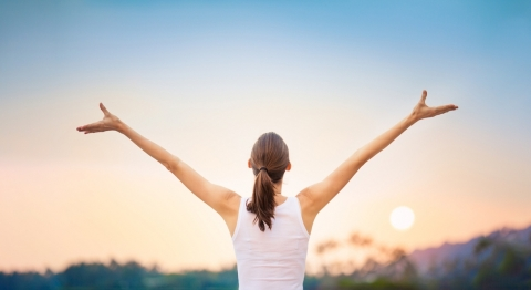 Young Woman Raising Her Arms Up Against the Sunset